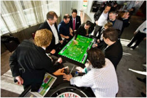 People admiring an electronic table game at a trade convention.